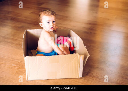 Baby Mädchen spielen, der in einer Kartonage verpackt mit Hilfe ihrer Phantasie. - Stockfoto