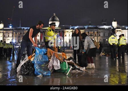 Die Demonstranten versammeln sich ihre Sachen wie die Arbeit der Polizei die letzten Aussterben Rebellion Demonstration in Trafalgar Square, Central London zu entfernen. - Stockfoto