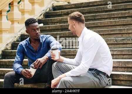Ernsthafte junge Schwarze Geschäftsmann trinken Kaffee und hören auf Kollegen, wenn sie ruhen auf Schritte - Stockfoto
