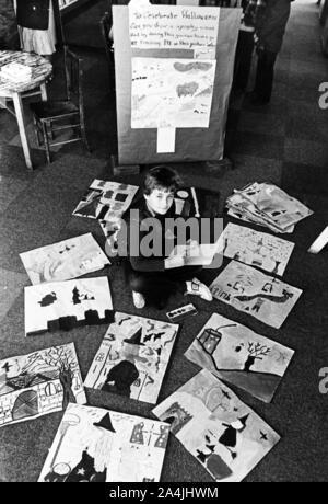 Ein Junge sitzt auf dem Boden unter Gemälde und Zeichnungen, die von Kindern für Halloween gemacht worden sind. 29. Oktober 1980. - Stockfoto