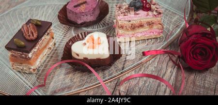 Konzept für ein Café oder eine Bäckerei mit Desserts, festliche Banner. Kleine Kuchen mit verschiedenen Füllungen in der Form eines Herzens - Stockfoto