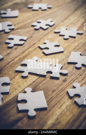 Zwei Teile eines Puzzles auf einer hölzernen Tisch verbunden mit vielen anderen Teile des Puzzles. Problemlösung Konzept. - Stockfoto
