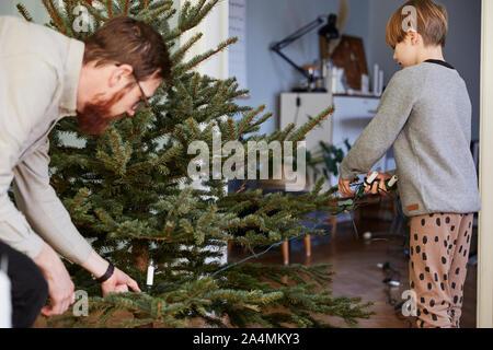 Vater und Sohn schmücken Weihnachtsbaum - Stockfoto