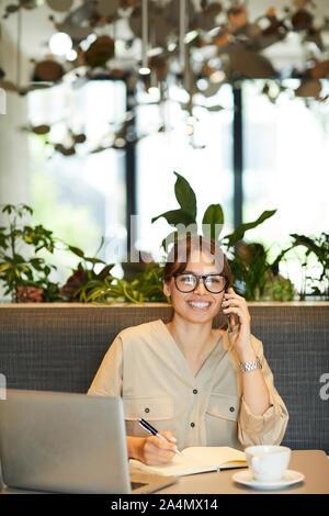 Glückliche junge geschäftsfrau in Brillen am Tisch vor Laptop sitzen und sich Notizen in Notepad, während Sie telefonieren im Cafe - Stockfoto