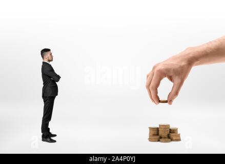 Geschäftsmann auf der Hand eines großen Mann, der Stapel von Goldmünzen auf weißem Hintergrund suchen - Stockfoto