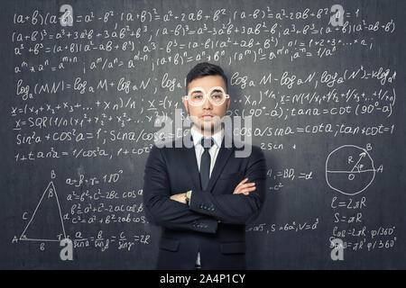 Unternehmer, die auf dem Hintergrund der Tafel mit mathematischen Formeln. - Stockfoto