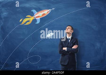 Ein Geschäftsmann, der mit seinen Armen auf dem dunkelblauen Hintergrund gefaltet, er ist auf der Suche, die Bilder von der Rakete und das UFO auf der Wand gezeichnet. - Stockfoto