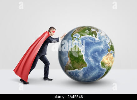 Ein Geschäftsmann in einen Superhelden red Cape schieben und Rollen eine große Kugel auf weißem Hintergrund. - Stockfoto