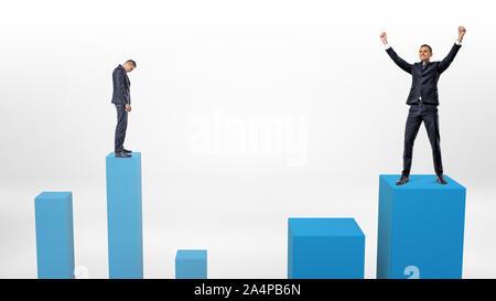 Eine traurige Geschäftsmann bereitet sich auf einen niedrigen Spalte und einen Sieger neben ihm, die gerade verstärkt auf eine höhere zu Schritt. - Stockfoto