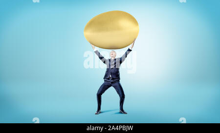 Ein glückliches Geschäftsmann auf blauem Hintergrund hält eine riesige goldene Ei über seinen Kopf. - Stockfoto