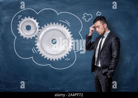 Ein Geschäftsmann denkt mit seinen Fingern berühren die Stirn, während in der Nähe von Metall Zahnräder innerhalb ein Gedanke Blase stehen. - Stockfoto