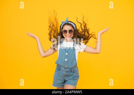 Ihre Frisur den ganzen Tag dauern. Glückliches Kind mit Curly Frisur fliegen auf gelben Hintergrund. Kleine süße Mädchen lächelnd mit Lange wellige Frisur. Mode Aussehen der Frisur mit glamourösen Locken. - Stockfoto