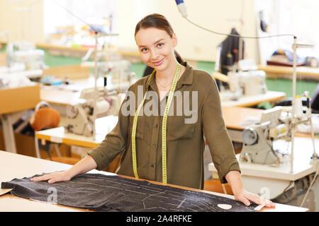 Porträt der jungen Frau, die in der Nähe ihres Arbeitsplatzes mit Stoff und Kamera in der Werkstatt - Stockfoto