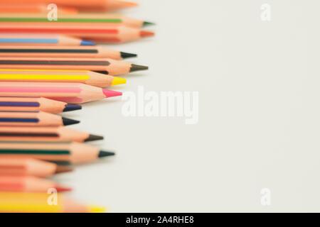 Spitzen Buntstifte, die von der linken Hintergrund Papier, der Weiss erscheinen, in der Tiefe ausgerichtet. - Stockfoto