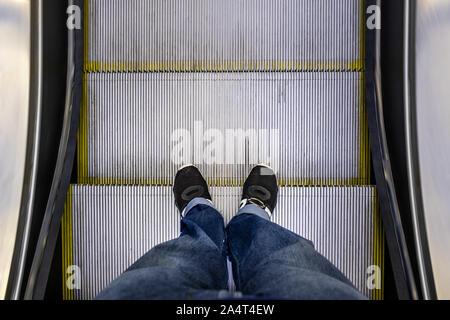 Männliche Füße in Jeans und schwarze Turnschuhe stehen auf Rolltreppe POV - Stockfoto