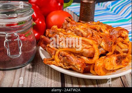 Lamm Rippchen mariniert mit Gewürzen in einen Teller auf dem Tisch. Mit Tomaten, Paprika und ein Glas Gewürze - Stockfoto