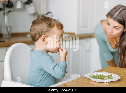 Charmante konzentriert baby boy Essen zunächst Essen Grüne Traube auf die helle Küche zu Hause
