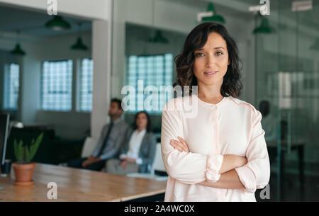 Lächelnden jungen Geschäftsfrau selbstbewusst in einem großen Büro - Stockfoto
