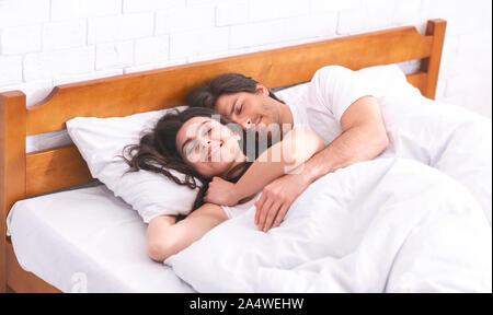 Liebevoller Mann und Frau schlafen im Bett, einander umarmen - Stockfoto