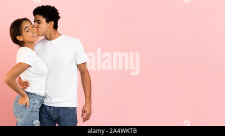 Afro Kerl küsst Freundin in Wange, rosa Hintergrund - Stockfoto
