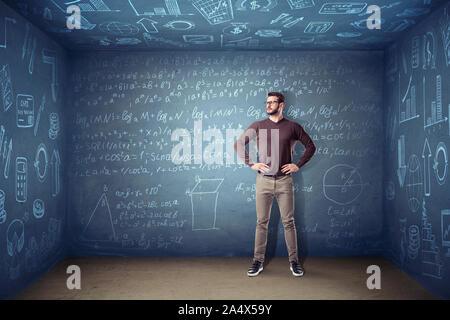 Ein Mann in Gläsern steht in einem kleinen quadratischen Raum, wo die Wände mit Kreide Gleichungen und Diagrammen abgedeckt sind. Wissenschaft und Wissen. Erfinder und Engin - Stockfoto