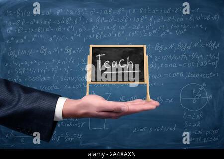 Die Hand eines Geschäftsmann hält eine kleine Staffelei Tafel mit einem Wort Lehren mit Gleichungen auf dem Hintergrund. Bildung und Nachhilfe. Mathematische Probleme. S - Stockfoto