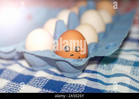 Weißes huhn eier in einem offenen Karton, lustig, eine von zehn Eier, Braun.. - Stockfoto
