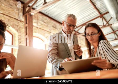 Die gemeinsame Nutzung von Erfahrungen. Älterer Mann in formale Abnutzung holding Tasse Kaffee und etwas zu erklären, seine junge Kollegin, während sich die Zusammenarbeit in der - Stockfoto