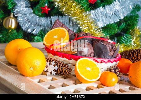 Weihnachtsfeiertag noch Leben mit Nahaufnahme Cupcakes, Zimtstangen, Orangen, Schokolade und Pine Cone auf Weihnachtsbaum Hintergrund - Stockfoto