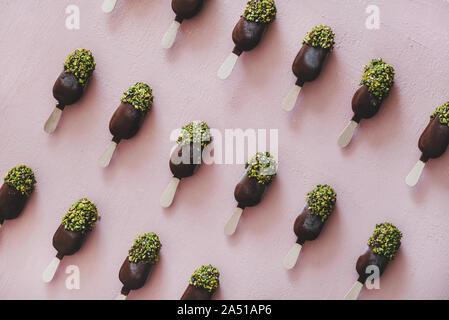 Schokolade glasiert popsicle Eis mit Pistazien Puderzucker über rosa Hintergrund - Stockfoto