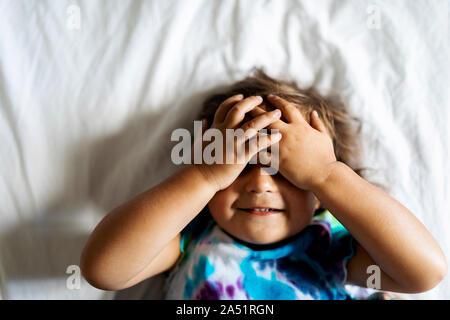 Kleinkind Mädchen liegt auf dem Bett und ihre Augen - Stockfoto