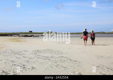 Junges Paar gehen über den Sand bei Ebbe, von North Uist zur unbewohnten Insel Vallay, auf den Äußeren Hebriden, Schottland, Großbritannien - Stockfoto