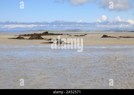 Blick von North Uist, über das Wattenmeer und nassen Sand bei Ebbe, auf die Insel Vallay, auf den äusseren Hebriden von Schottland, Großbritannien - Stockfoto