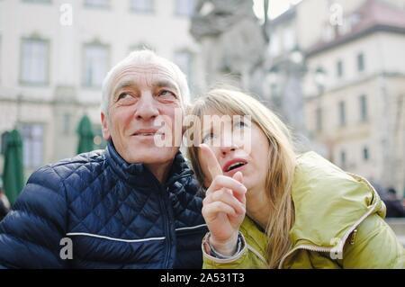 Im freien Portrait von älteren Mann und seine junge blonde Frau Ausgabe Zeit zusammen in der alten Stadt im frühen Frühjahr oder Herbst. Paar mit Alter - Stockfoto