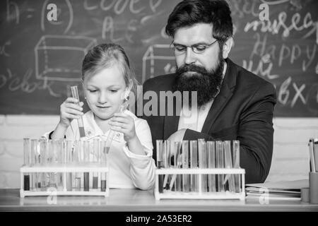 Schule Chemie Experiment. Chemie zu erklären Kid. Wie Interesse Kinder studieren. Faszinierende Chemie Lektion. Man bärtige Lehrer und Schüler mit Reagenzgläsern im Klassenzimmer. Privatunterricht. - Stockfoto