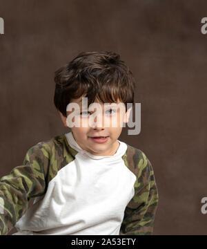Vertikale studio Shot eines Verdächtigen, aber niedlichen vier Jahre alten auf braunem Hintergrund mit kopieren. - Stockfoto