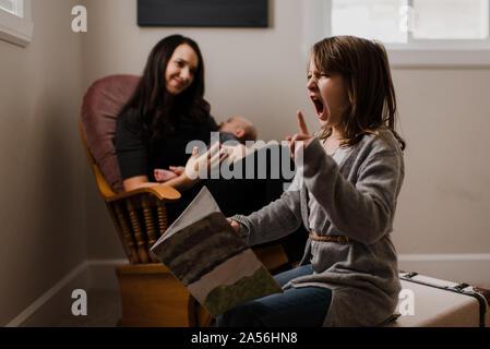 Mädchen mit Buch Gesichter ziehen, während Mutter wiegen baby Bruder in Wohnzimmer Sessel Stockfoto