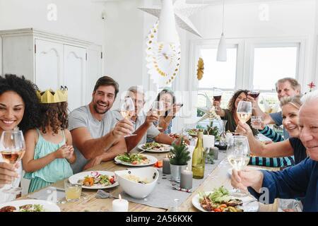 Familie toasten Wein am Esstisch in Home Party - Stockfoto