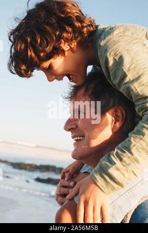 Vater und Sohn Huckepack Reiten am Strand - Stockfoto
