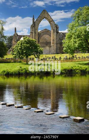 12. jahrhundert Augustiner Bolton Priory Kirche Ruinen mit Friedhof und Trittsteine in River Wharfe in Bolton Abbey England - Stockfoto
