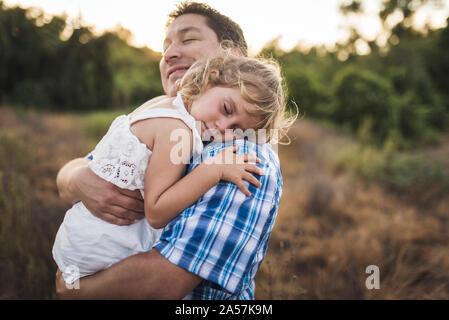 Lächelnd Vati knuddel Kind schlafen auf seiner Schulter