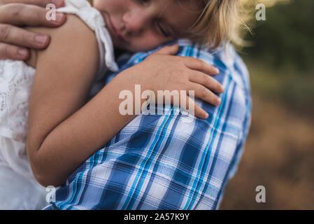Schlafende Kind kuschelt auf die Schulter ihres Vater in eine sonnige Wiese