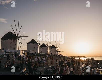 Mykonos, Griechenland - 23. September 2019: Leute beobachten Sonnenuntergang in der Nähe der Windmühlen in Hora (Mykonos Stadt), die Hauptstadt der Insel und eines der besten Beispiele