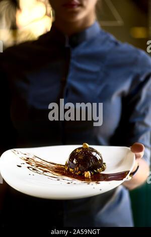 Französische mini Mousse Gebäck Dessert Schokolade Sahnehäubchen auf einem Teller. Dessert in den Händen einer Kellnerin. Nach oben Schließen - Stockfoto