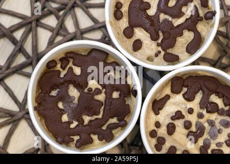 Gesund vegan süße Nachspeise. Raw Banane Eiscreme mit Kokosnuss Creme beschichtet mit natürlichen Schokolade Tröpfchen in einem White Paper cups auf Tisch - Stockfoto
