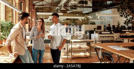 Schön reden. Drei junge Kollegen in Freizeitkleidung holding Kaffeetassen und etwas diskutieren beim Stehen im modernen Büro - Stockfoto