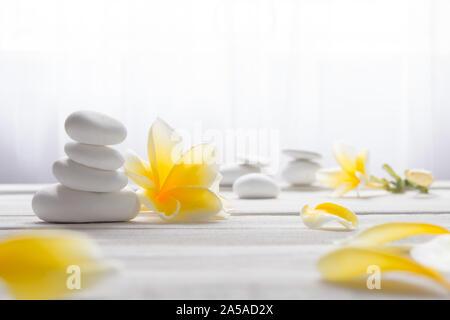 Gestapelte Steine weiß auf weißem Hintergrund mit gelben frangapani Blume - Lebensstil und alternative Health Concept Bild mit Kopie Platz für Text. - Stockfoto