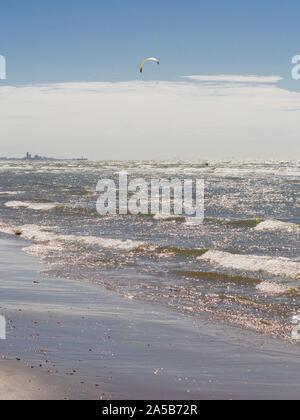 Vorbei vor der Skyline von Den Haag (Den Haag), ein Kite Surfer genießt die stürmische Nordsee auf einem Strand von Katwijk, Niederlande. - Stockfoto