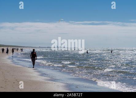 Vor der Skyline von Den Haag (Den Haag), Kitesurfer und Touristen genießen die stürmische Nordsee auf einem Strand von Katwijk, Niederlande. - Stockfoto