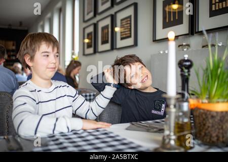Zwei Jungen warten auf Pizza im Restaurant. - Brüder, Spaß zu haben. - Stockfoto